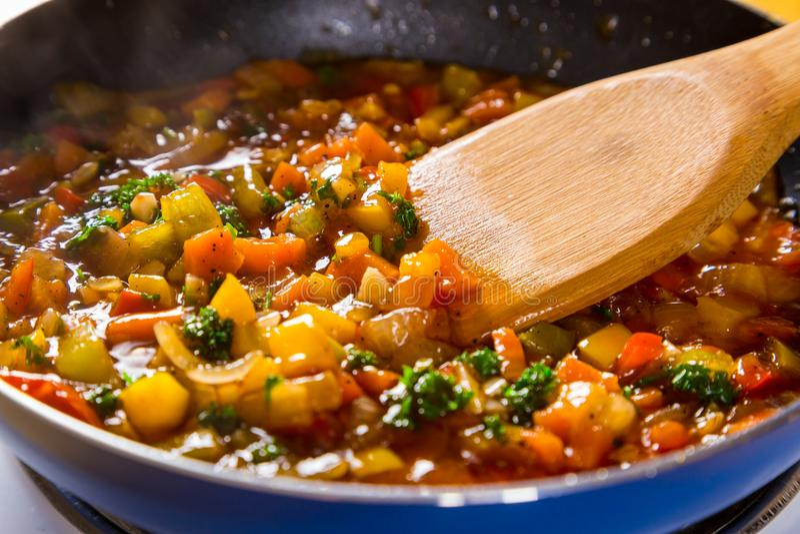 Vegetais coloridos cozidos cortados na frigideira fotos de stock