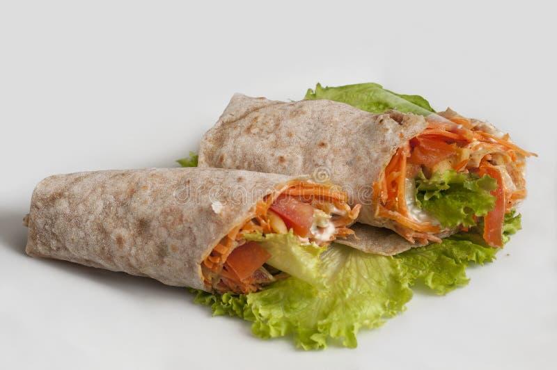 Vegetais com o creme de leite, envolvido no pão do pão árabe em um fundo branco imagens de stock