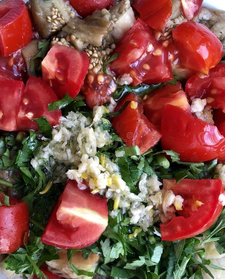 Vegetais cortados: beringelas cozidas, alho, tomates frescos, salsa imagem de stock royalty free