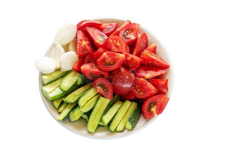 Vegetais cortados Tomates, pepinos e cebolas em um fundo cinzento Trajeto de grampeamento foto de stock royalty free