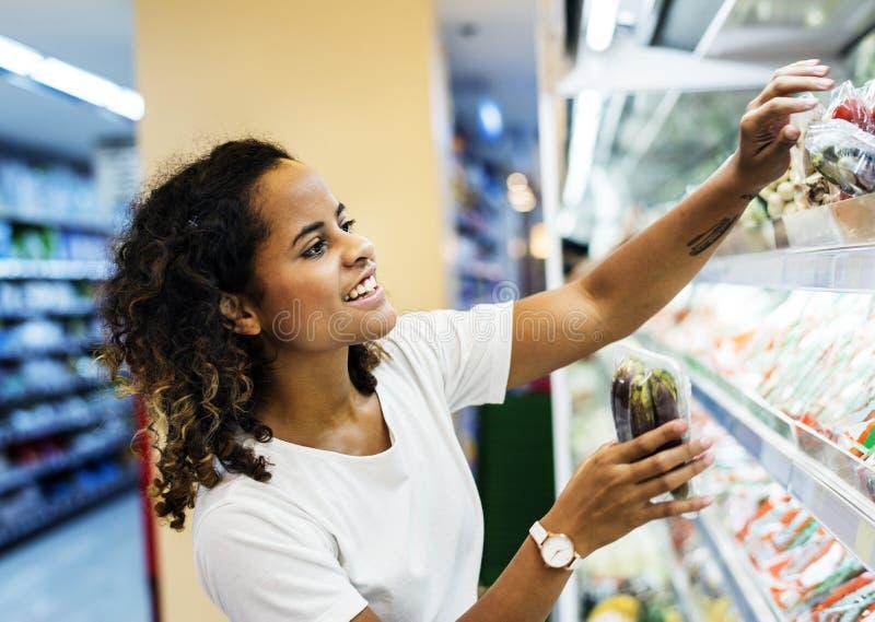 Vegetais da compra da mulher no supermercado fotografia de stock royalty free