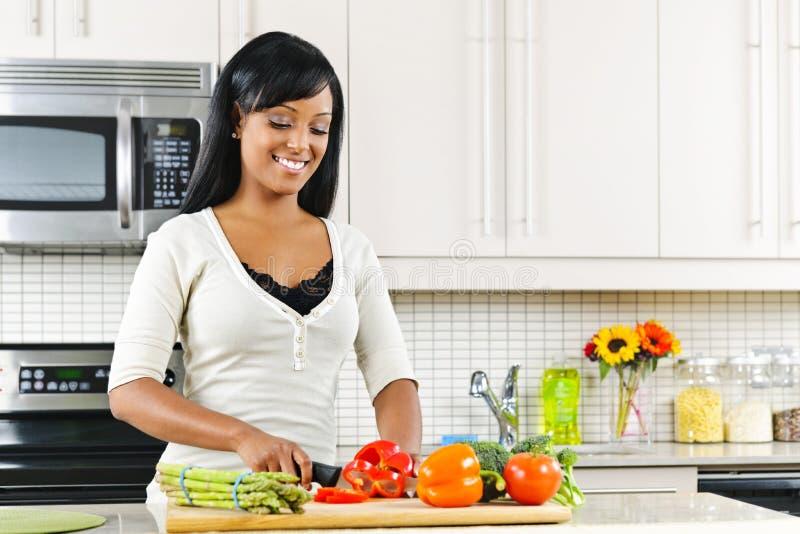 Vegetais da estaca da mulher nova na cozinha fotografia de stock