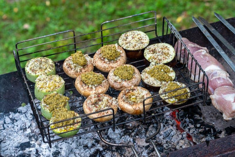 Vegetais da repreensão com queijo e especiarias na grade Cogumelos, beringelas e abobrinha de cozimento no carvão vegetal fotos de stock royalty free