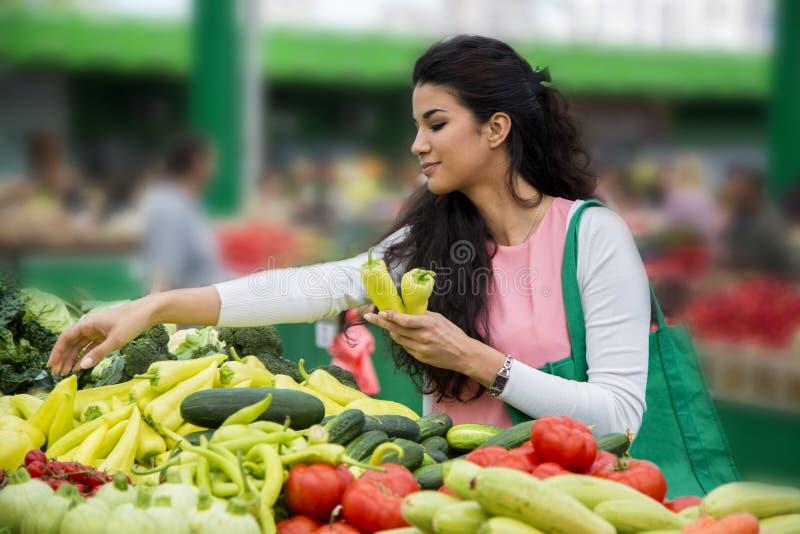 Vegetais de compra da mulher no mercado fotos de stock royalty free