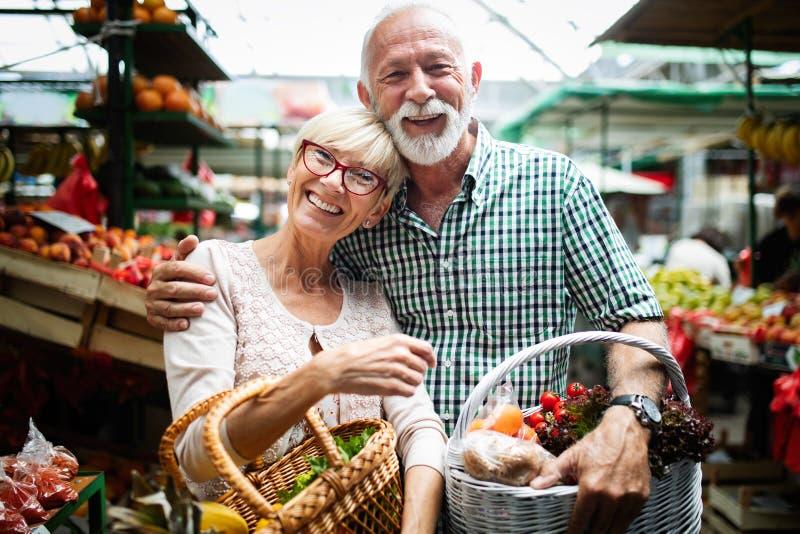 Vegetais de compra de sorriso dos pares superiores e no merket imagens de stock royalty free