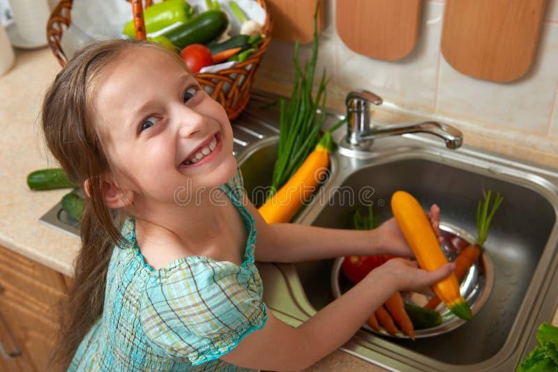 Vegetais de lavagem da menina da criança e frutos frescos na cozinha interior, conceito saudável do alimento fotos de stock royalty free