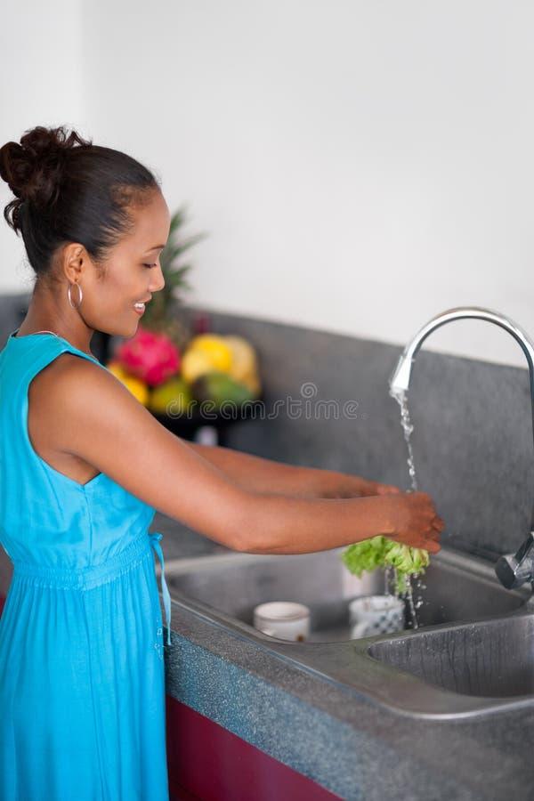 Vegetais de lavagem da mulher nova do Balinese fotos de stock royalty free