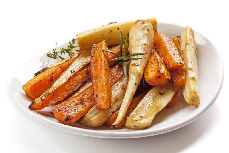 Vegetais de raiz Roasted no prato branco isolado imagem de stock