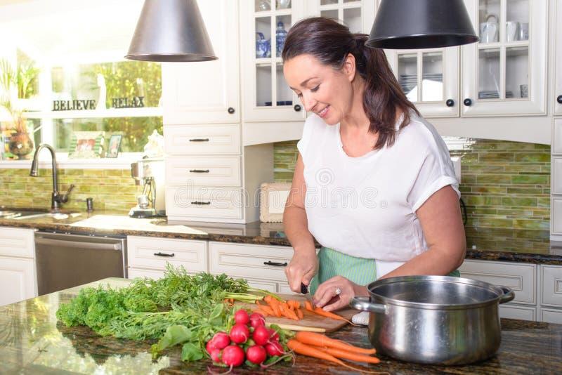 Vegetais de sorriso atrativos do corte da mulher em sua cozinha ensolarada imagens de stock