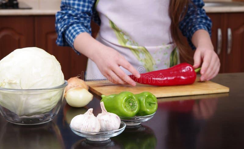 Vegetais do corte da menina para o close up da salada imagem de stock