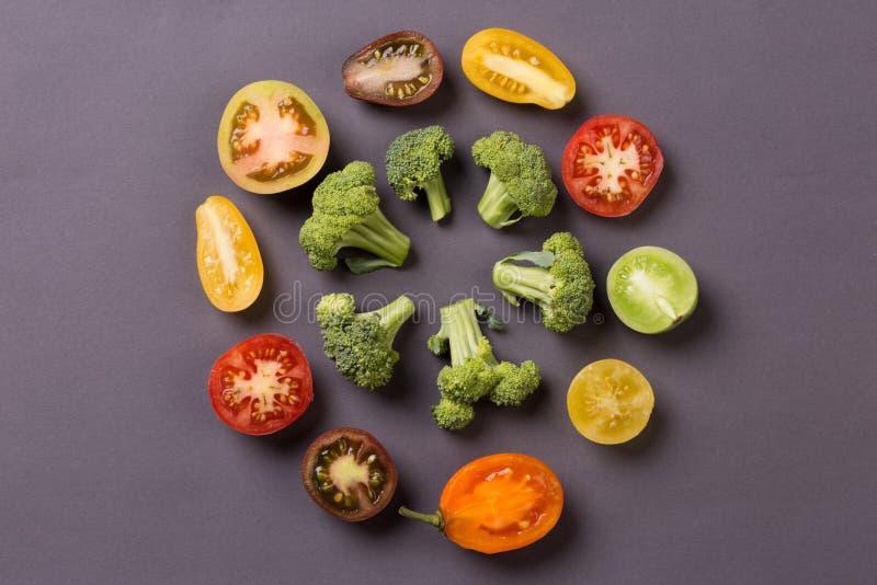 Vegetais do corte - tomate, brócolis no fundo cinzento imagem de stock royalty free
