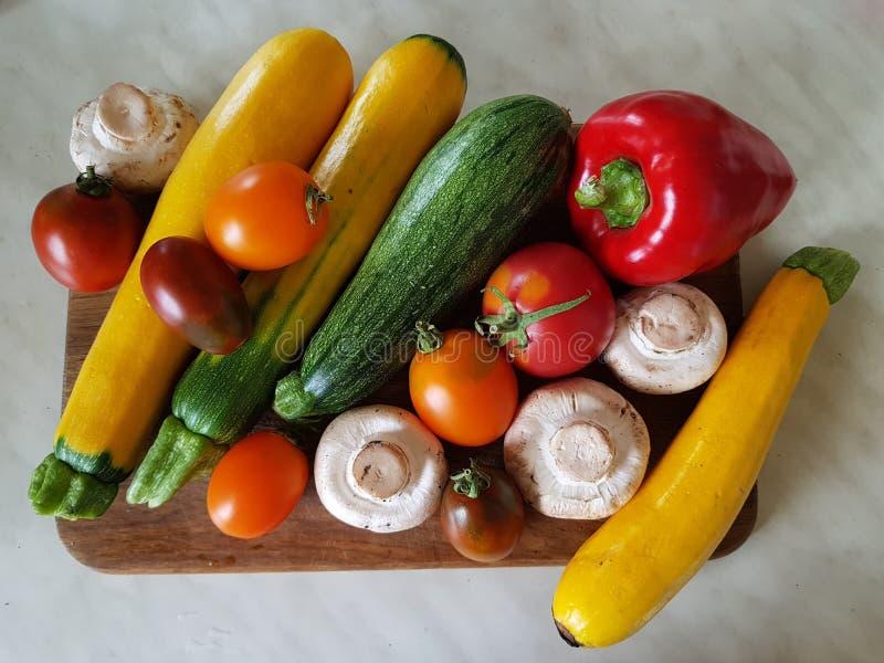 Vegetais do outono na mesa de cozinha Close-up dos vegetais Tomates, abobrinha, cogumelos da pimenta Vermelho, amarelo, branco, v imagem de stock royalty free
