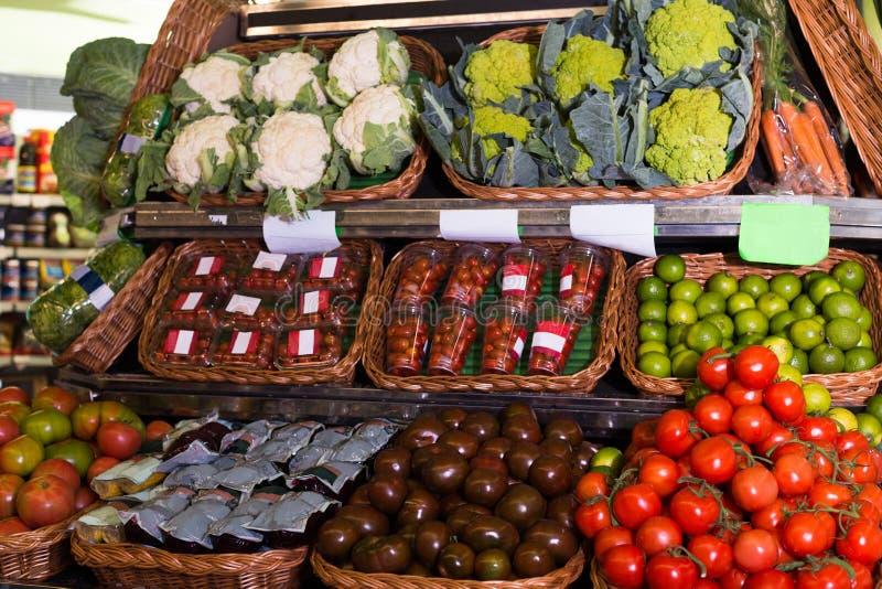 Vegetais e frutos em cestas de vime no contador do greengrocery imagens de stock