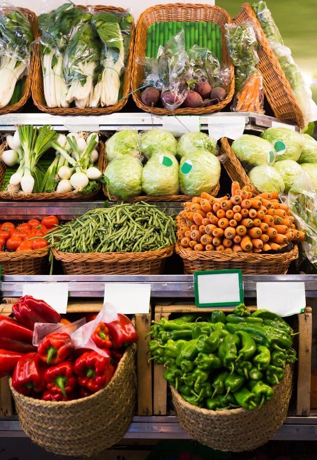 Vegetais e frutos em cestas de vime no contador do greengrocery imagem de stock