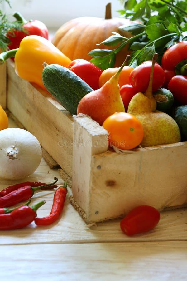 Vegetais e frutos em uma caixa de madeira imagens de stock
