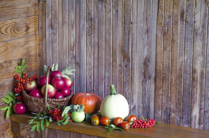 Vegetais e frutos em uma cesta em um fundo de madeira colhendo a abóbora da colheita do outono e do verão, abobrinha, maçã, fotos de stock
