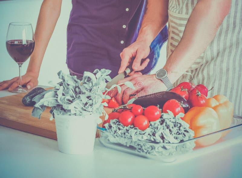 Vegetais e mulher do corte do homem novo que estão na cozinha fotografia de stock