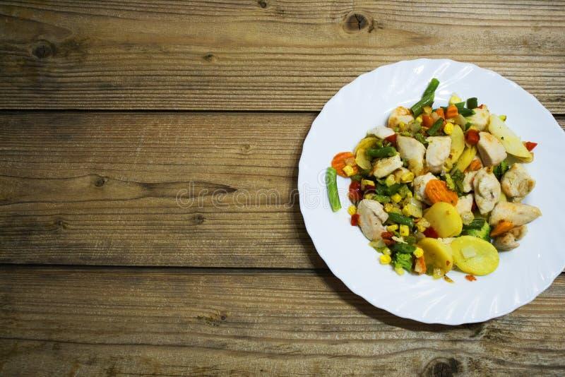Vegetais e peito de frango na tabela de madeira imagem de stock