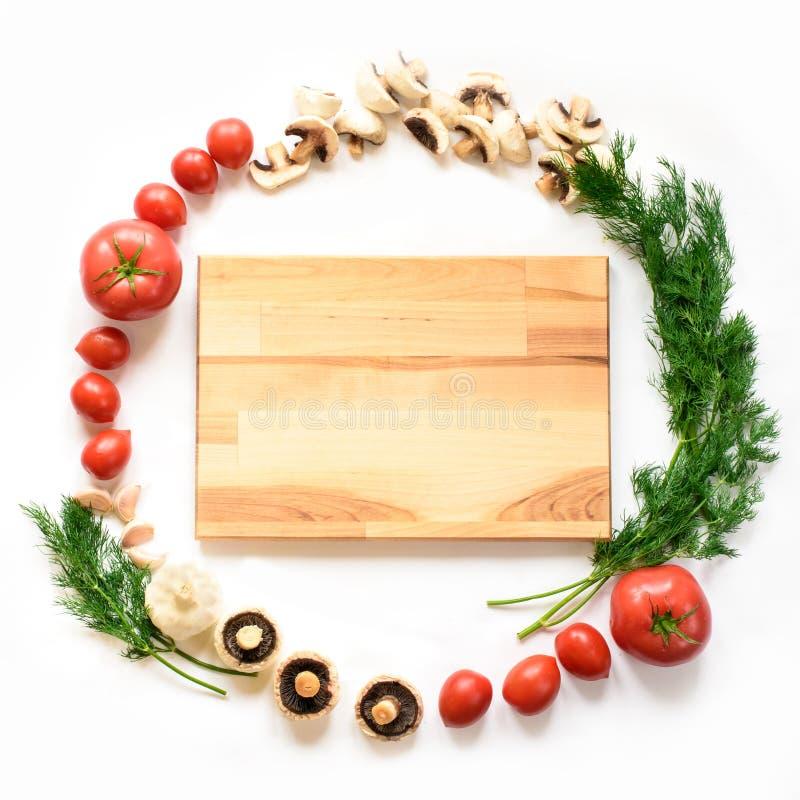 Vegetais em torno da placa de corte vazia no fundo branco, vista superior fotos de stock royalty free