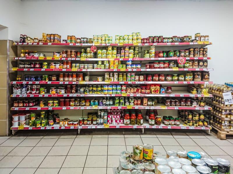 Vegetais enlatados nas prateleiras de um supermercado do mantimento foto de stock
