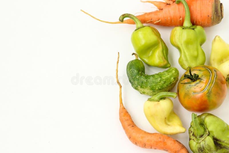 Vegetais feios: cenouras, pepino, pimentas e tomates no fundo branco, conceito feio do alimento, espaço da cópia fotografia de stock