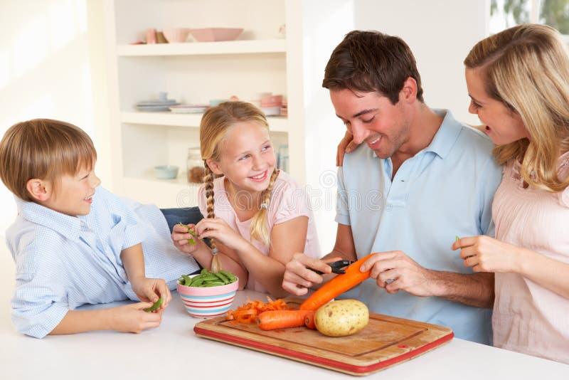 Vegetais felizes da casca da família na cozinha imagem de stock