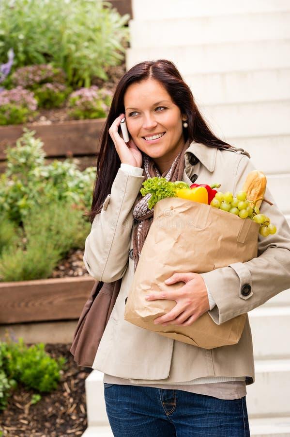 Vegetais felizes da compra da mulher que chamam o telemóvel foto de stock royalty free