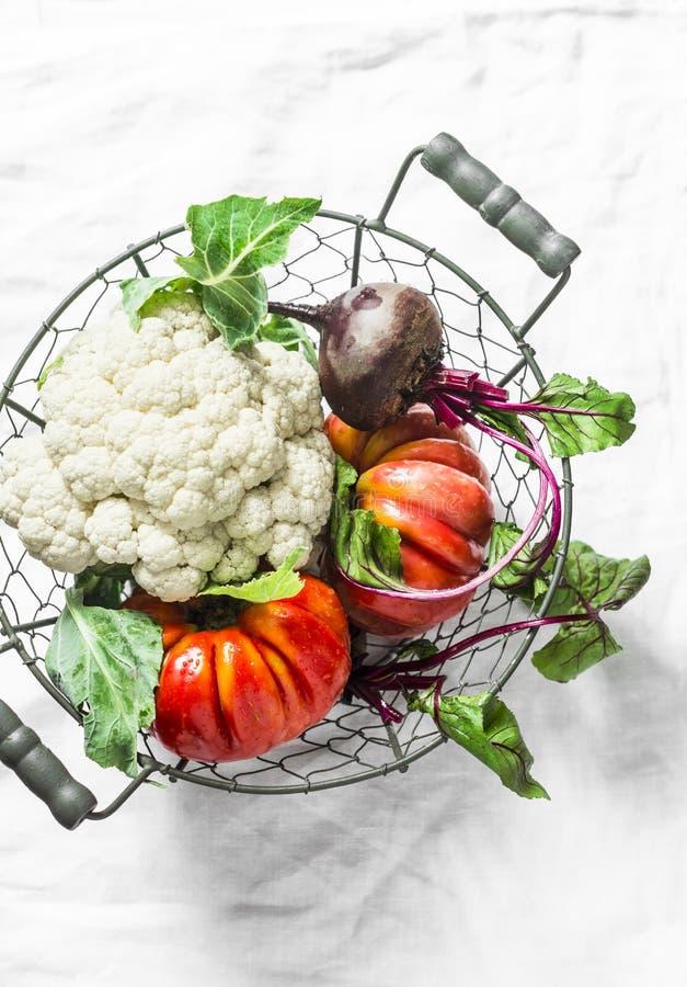 Vegetais orgânicos frescos - a couve-flor, tomates da herança, beterrabas no vintage metal a cesta no fundo claro fotos de stock