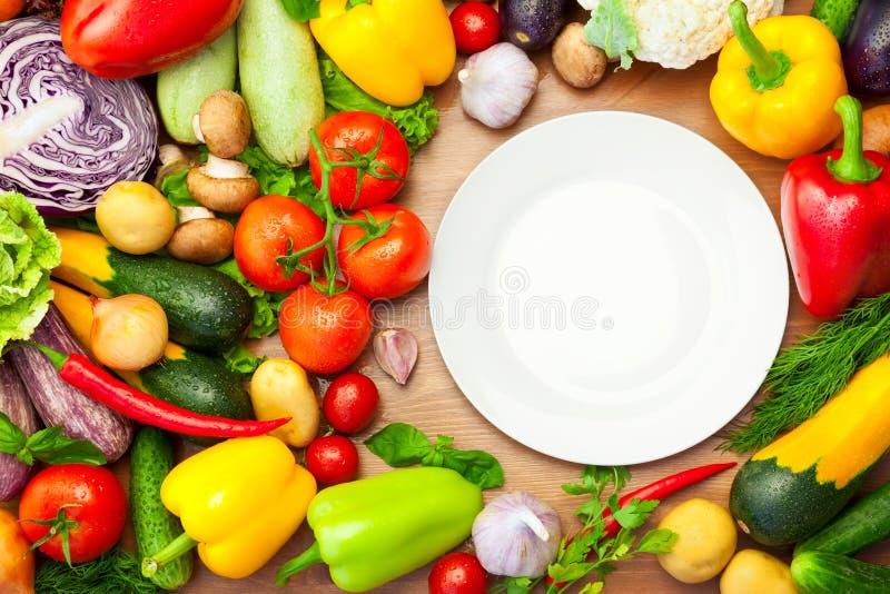 Vegetais orgânicos frescos em torno da placa branca fotos de stock royalty free