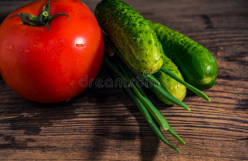 Vegetais orgânicos frescos para a salada no fundo rústico Tomate, pepinos, close-up das cebolas imagem de stock royalty free