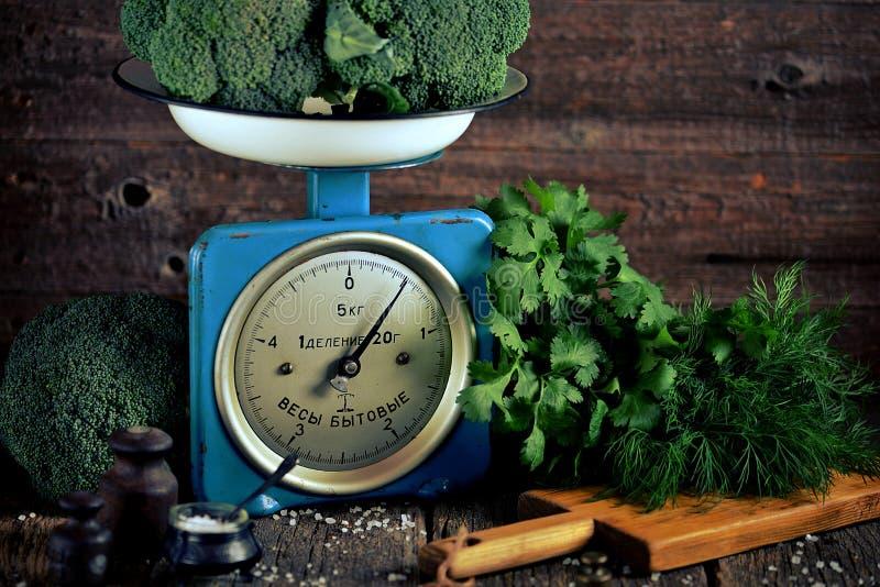 Vegetais orgânicos saudáveis brócolis e couve-de-milão em escalas mecânicas soviéticas velhas Estilo rústico do vintage imagens de stock royalty free