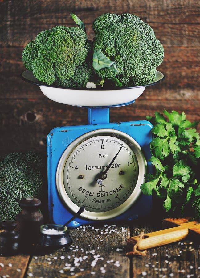 Vegetais orgânicos saudáveis brócolis e couve-de-milão em escalas mecânicas soviéticas velhas Estilo rústico do vintage fotografia de stock