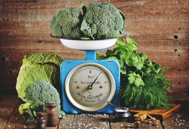 Vegetais orgânicos saudáveis brócolis e couve-de-milão em escalas mecânicas soviéticas velhas Estilo rústico do vintage imagem de stock