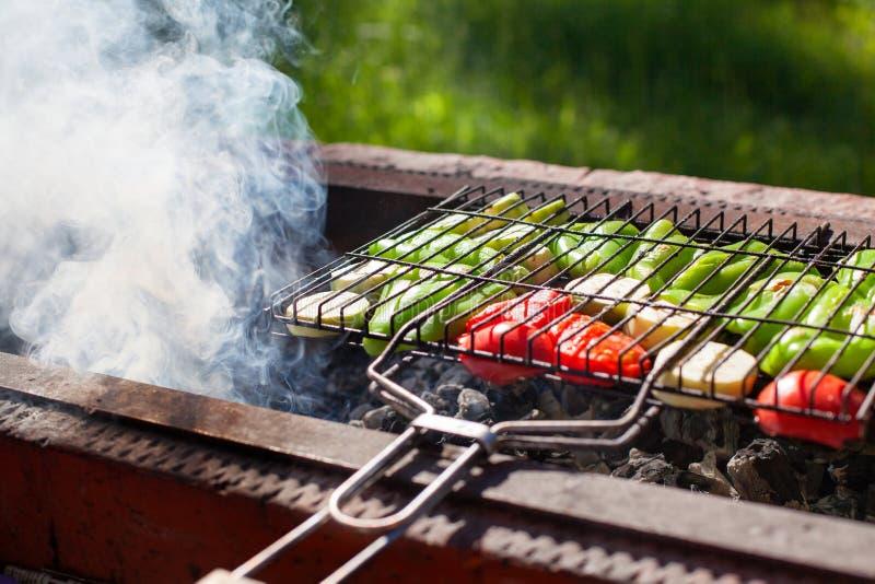 Vegetais roasted na grade no carvão vegetal, fumo do fogo, natureza, fundo da grama verde, pimentas verdes, abobrinha, tomates ve foto de stock royalty free