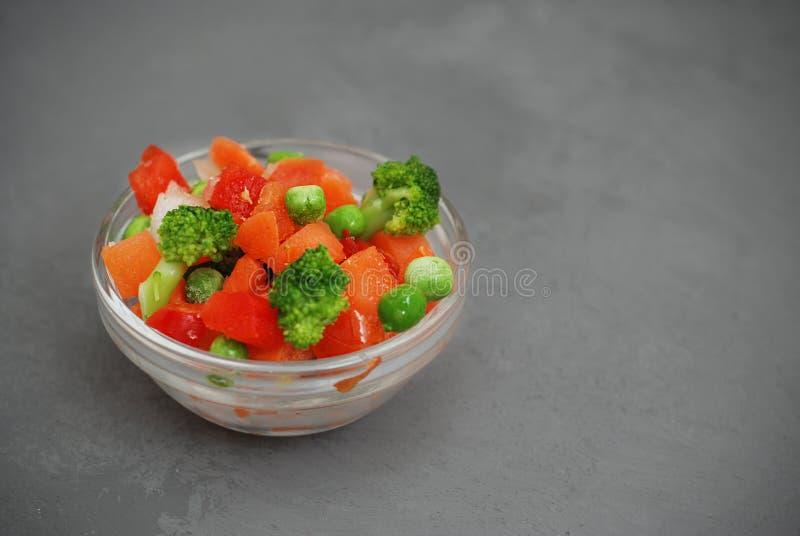 Vegetais saudáveis congelados do vegetariano colorido Brocolli, cenouras, ervilhas, pimenta Imagem vertical Fundo cinzento fotografia de stock