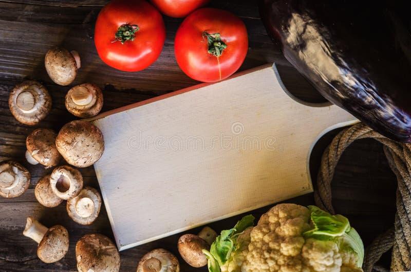 Vegetais saudáveis frescos na tabela de madeira com trencher branco Estilo rústico fotos de stock royalty free