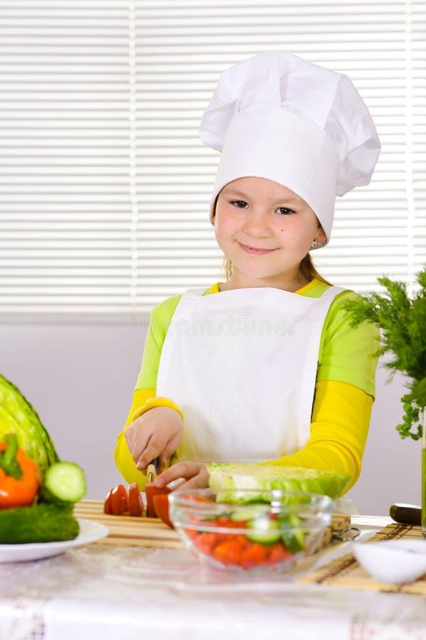 Vegetais uniformes vestindo do corte do cozinheiro chefe da menina fotos de stock