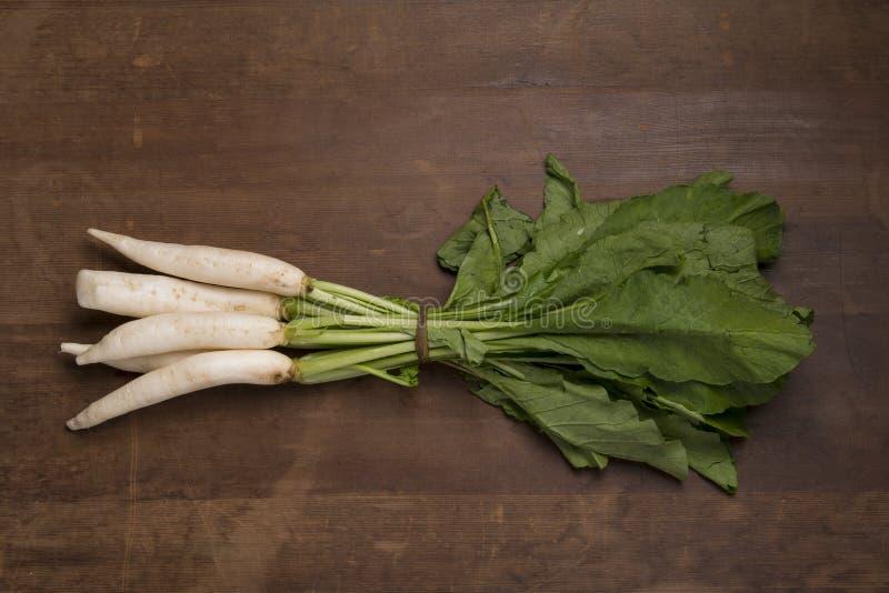 Vegetal: Ideia superior do grupo dos rabanetes no fundo de madeira imagem de stock