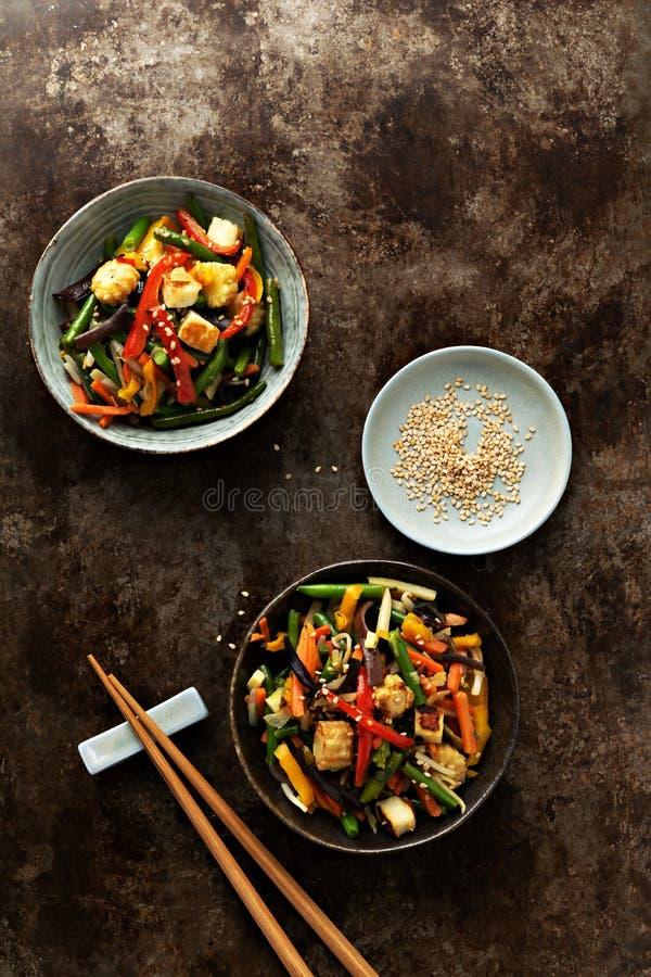 Vegetal na fritada da agitação da bacia no frigideira chinesa no fundo escuro concreto fotos de stock royalty free