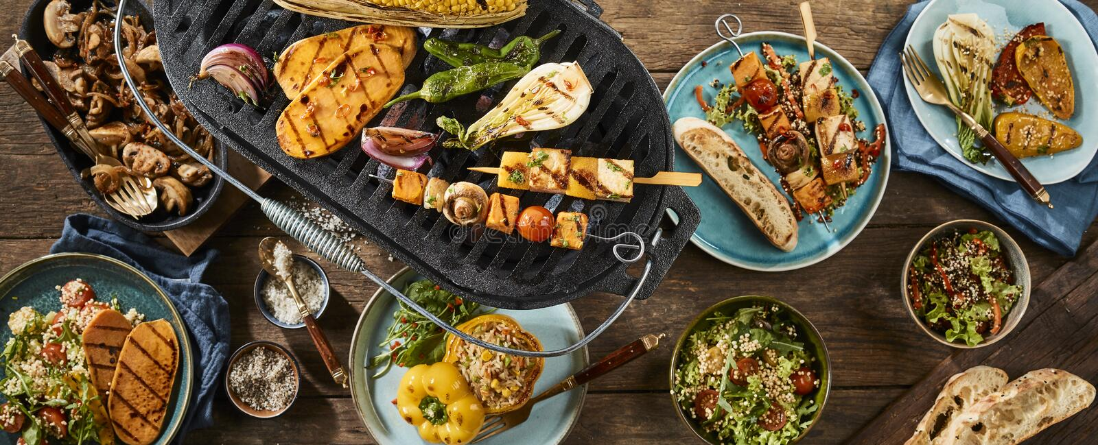 Vegetarian barbecue grilled dishes on timber table royalty free stock photo