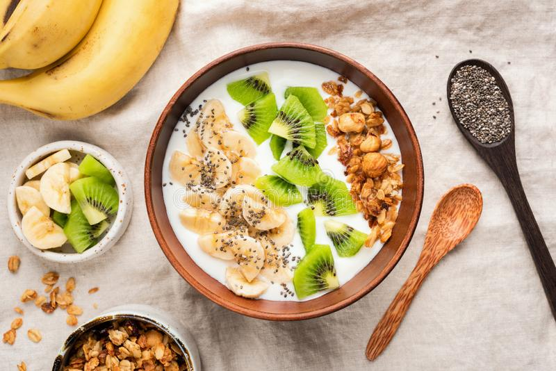 Vegetarian Breakfast Bowl With Yogurt Granola Fruits. Kiwi Banana Chia Seeds. Table top view. Concept of healthy eating, clean eating, dieting royalty free stock photo