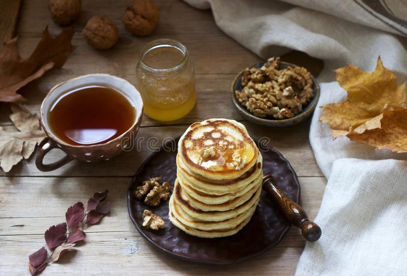 Vegetarian breakfast of fritters with honey, nuts and tea. Autumn still life. stock photography