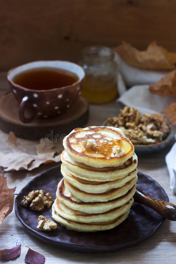 Vegetarian breakfast of fritters with honey, nuts and tea. Autumn still life. stock photos