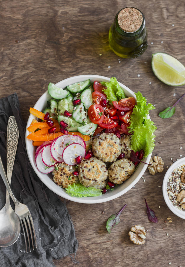 Vegetarian buddha bowl - quinoa meatballs and vegetable salad on wooden background, top view. Healthy, vegetarian food. Concept royalty free stock image