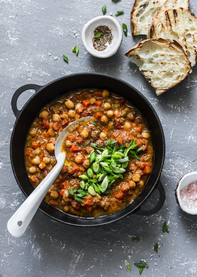 Vegetarian buffalo chickpea chili with mushrooms in a pan on a gray background, top view. Healthy vegetarian food royalty free stock image