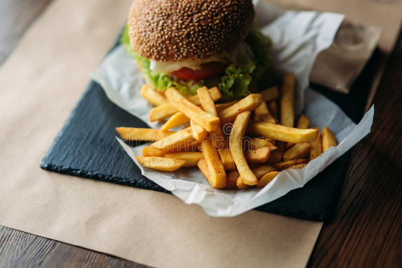 Vegetarian burger with french fries on a black tray in a cafe. Healthy food. vegetables stock photo