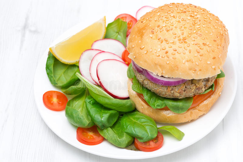 Vegetarian burger with fresh salad on the plate, top view stock images