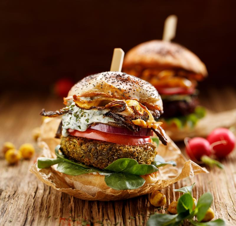 Vegetarian burger, green peas burger, homemade burger with green peas cutlet, grilled mushrooms, tomato, red onion, lamb`s lettuce stock photography