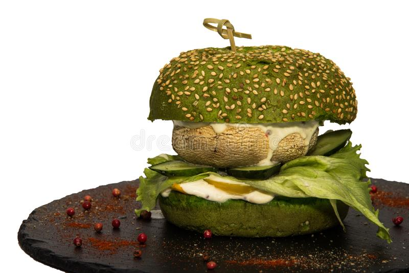 Vegetarian burger with a leaf of green salad, champignon, cucumbers and sauce. royalty free stock photography
