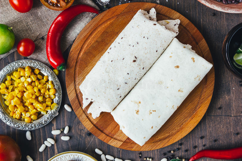 Vegetarian burrito on wooden board over black table surrounded by ingredients. Vegetarian burrito on wooden board over black table surrounded by ingredients stock photography